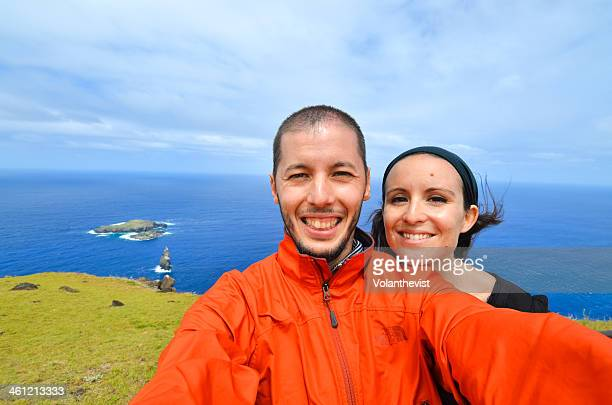 Happu young couple w/ Motu Nui and the sea behind