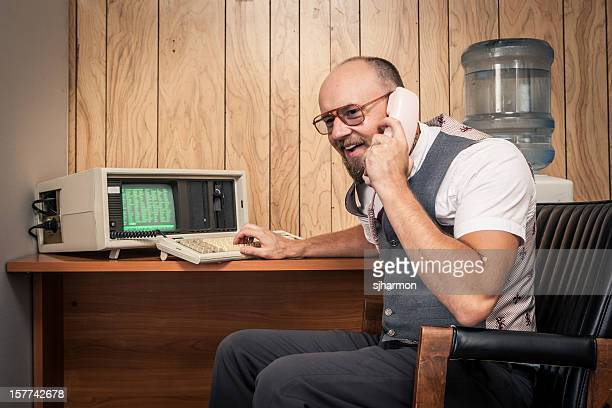 Happy 1980's computer worker nerd  on phone at cubicle