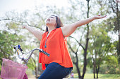 Happy a asian woman outstretched with bicycle outdoor in a park