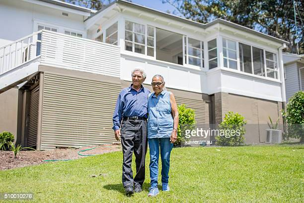 Happy aboriginal senior couple in front of their house