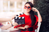 Diva in red dress and big shades starring in an artistic film