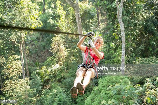 Felice donna avventurosa in zip-line attraversa la giungla