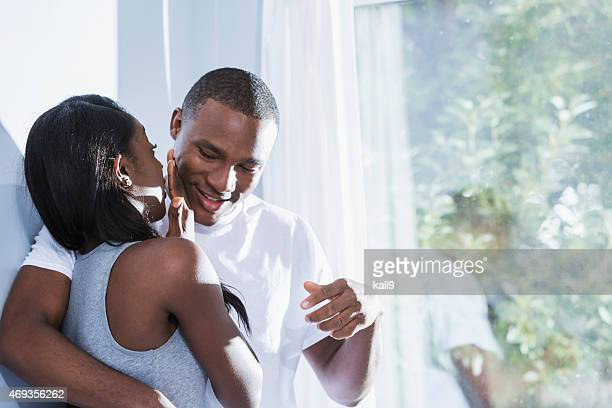 Happy affectionate black couple by sunny window