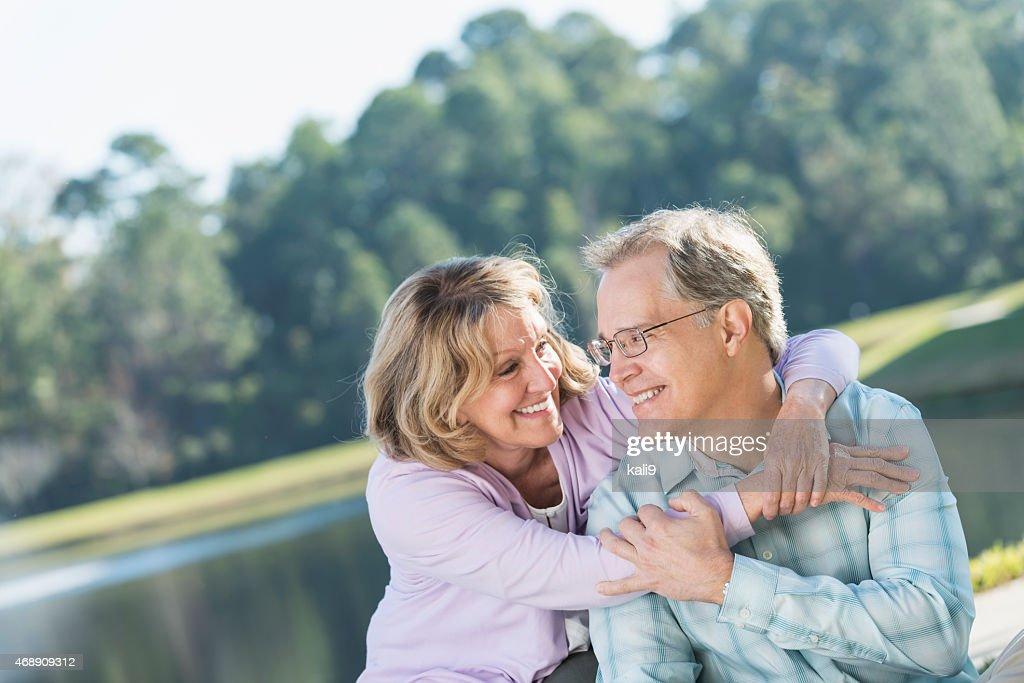 Heureux Affectueux couple d'âge mûr assis sur le lac : Photo