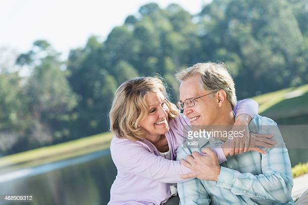 Happy affectionate mature couple sitting by lake