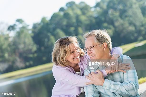 Glückliche Zärtlich Älteres Paar sitzt am See