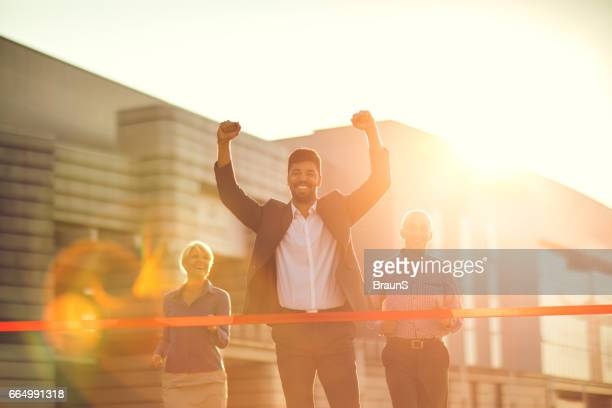 Happy African American businessman celebrating his victory in the race.