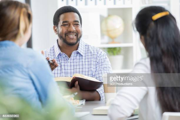 Happy African American businessman leads office Bible study