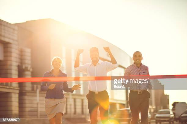 Happy African American businessman winning the race at sunset.