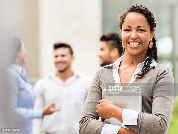 Happy African American businesswoman holding touchpad outdoors.