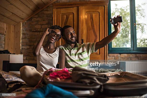 Happy African American couple filming themselves with video camera.
