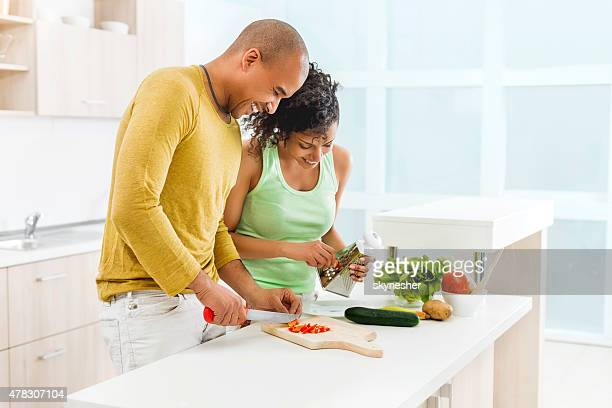 Happy African American couple making salad in the kitchen.
