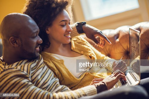 Happy African American couple online shopping at home.