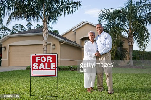 Happy African American couple outside house with for sale sign