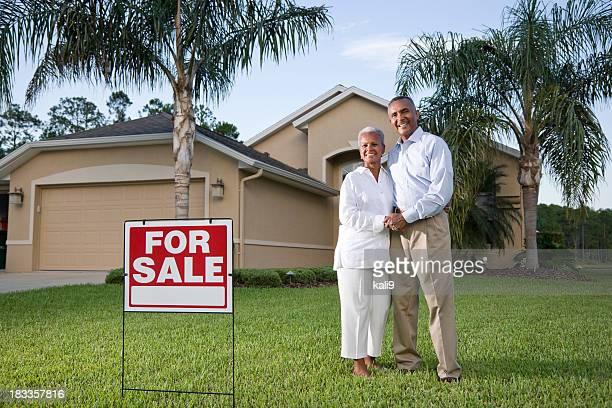Glückliche afroamerikanischen Paar außerhalb Haus mit für Verkauf Zeichen