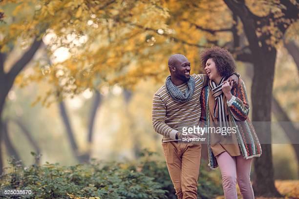 Glückliche afroamerikanischen Paar beim Gehen im Herbst park und viel miteinander lachen.
