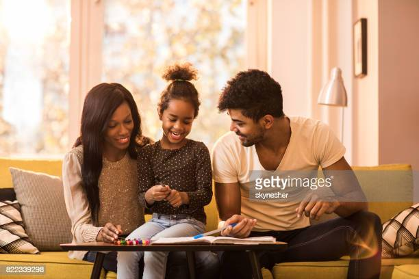 Happy African American family enjoying in creative time while drawing at home.