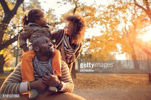 Feliz familia afroamericana disfrutando de la naturaleza durante el otoño.