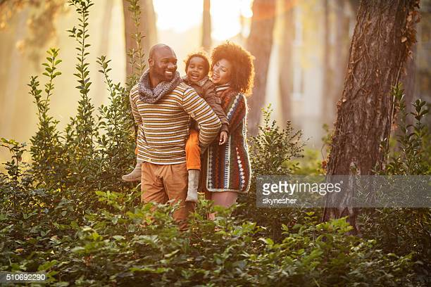 Happy African American family in nature at sunset.