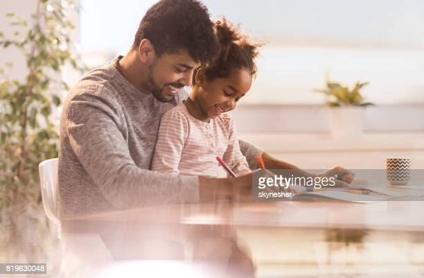 Happy African American father and daughter having fun while drawing at home.