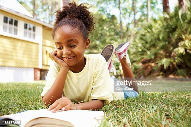 Happy African American girl reading book while lying on lawn