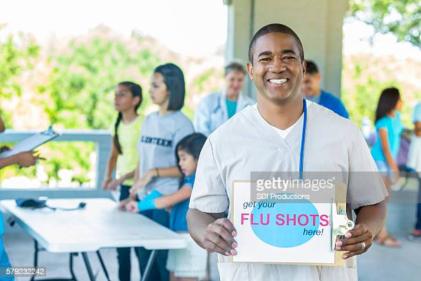 Happy African American male nurse holding flu shot sign