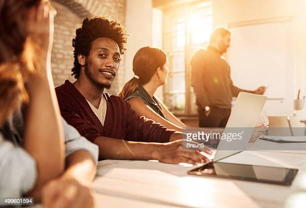 Heureux homme afro-américain assister à une présentation de la salle de conseil.