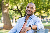 Young african man relaxing at park in a summer day. Happy black cheerful guy feeling good and sitting on bench at park. Smiling american man looking at camera outdoor.