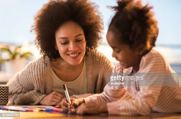 Happy African American mother and daughter spending creative time together.