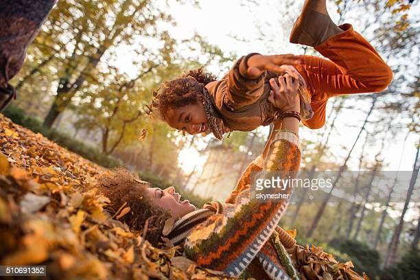 Glückliche afroamerikanischen Mutter spielen mit ihrer Tochter in Natur.
