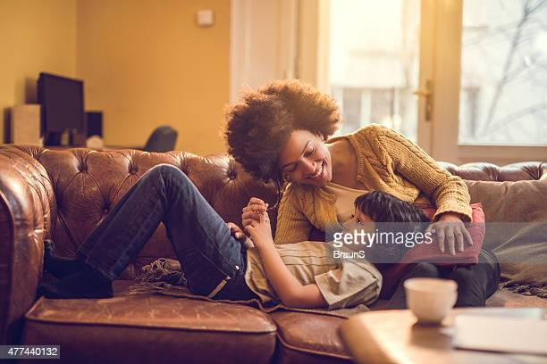 Happy African American mother relaxing with her son at home.