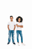 cute happy african american siblings standing together and looking at camera isolated on white