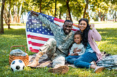 happy african american soldier in military uniform and family holding american flag in park