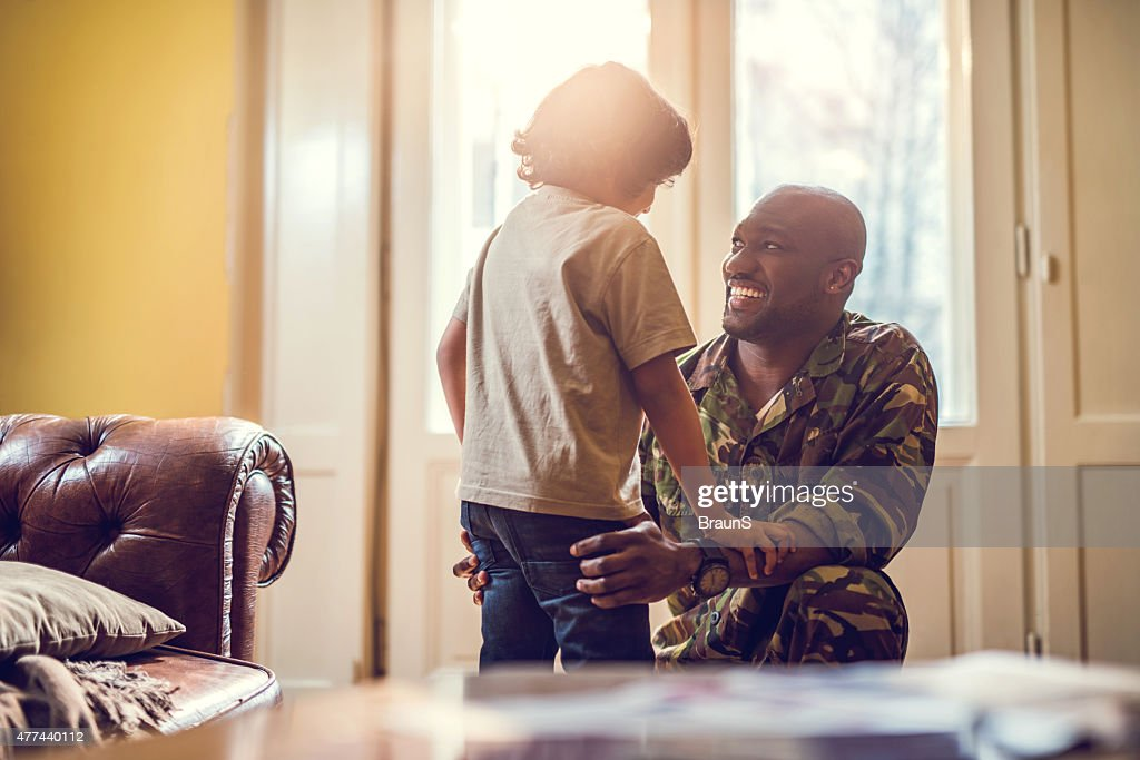 Happy African American soldier talking to his son at home. : Stock Photo