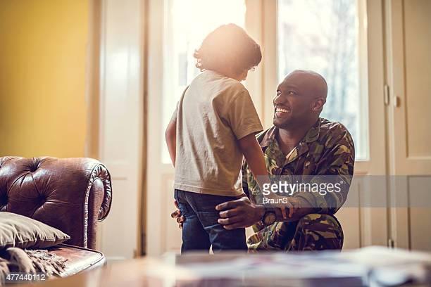Glückliche afrikanischen amerikanischen Soldaten im Gespräch mit seinem Sohn zu Hause fühlen.
