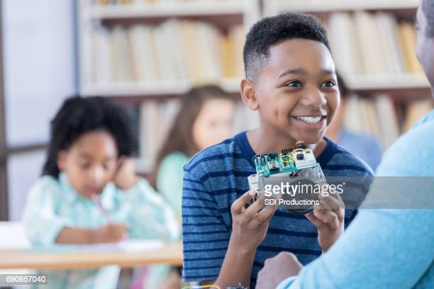 Happy African American student builds robot in class