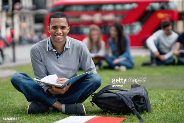 Happy African American student studying outdoors in London