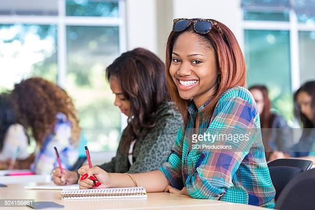 Happy African American student taking notes in college classroom