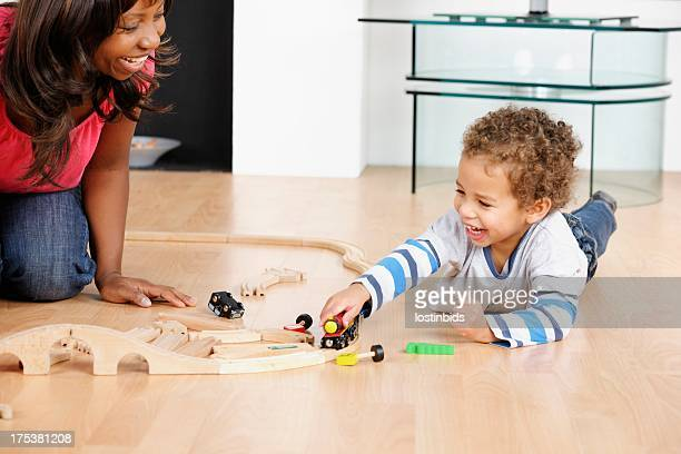 Happy African American Woman/ Carer And Toddler Playing With Trains