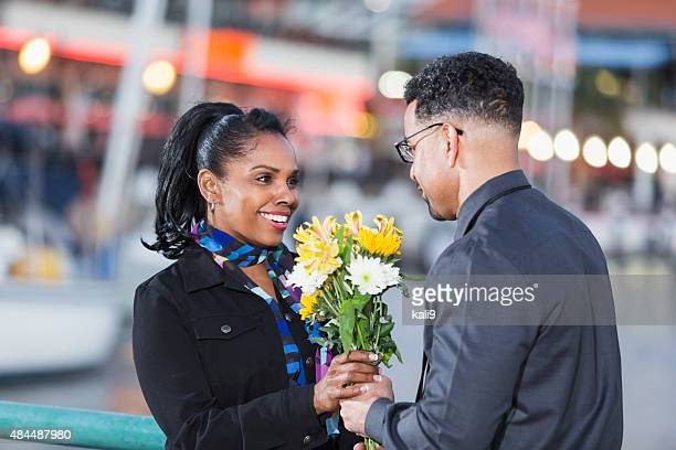 Happy African American woman getting flowers