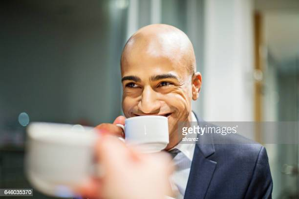 Happy african businessman having coffee