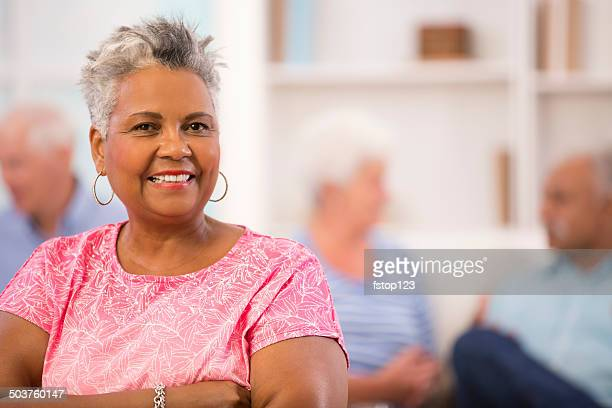 Happy, African descent senior woman. Home setting. Friends background.