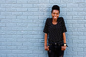 Portrait of happy young african female standing against gray brick wall with copy space