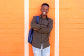 Portrait of happy young african male student standing against orange wall with bag