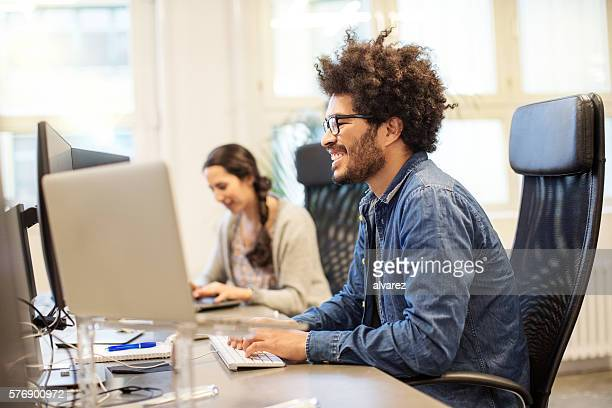 Happy african man working at his desk