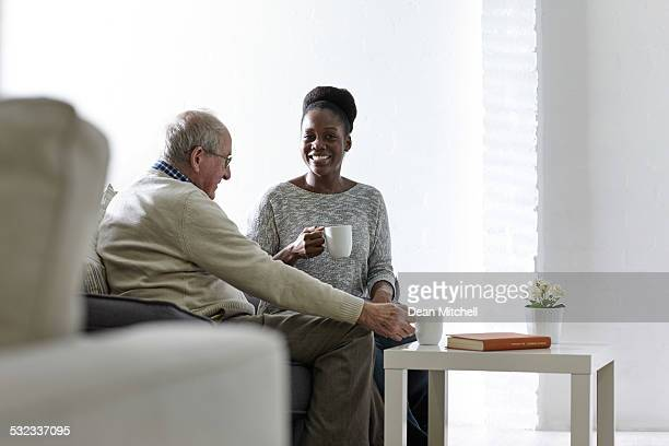 Feliz mujer africana con café con hombre senior en casa