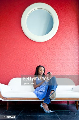Happy African woman texting in a hotel lounge