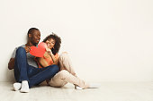 Young happy african-american couple in love holding red paper heart, sitting on floor of new flat, copy space. Family and valentine day concept, isolated