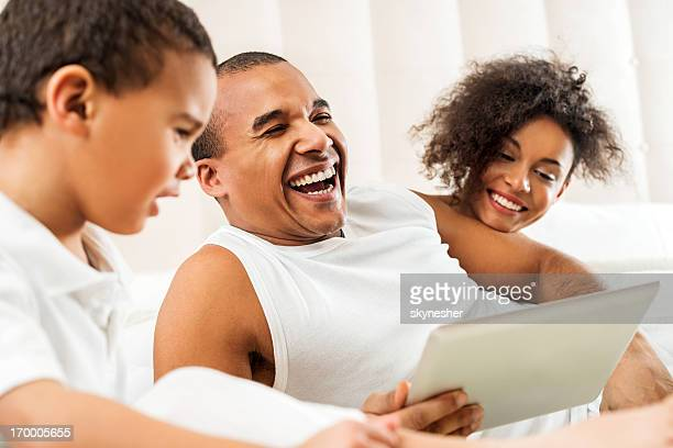 Happy African-American family in bed with digital tablet.
