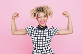 Studio portrait of excited afro american young woman flexing her muscles. Pink background.